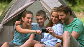 Cheerful family looking at photo on camera stock footage