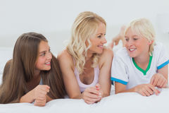 Cheerful family lying on bed Royalty Free Stock Photos