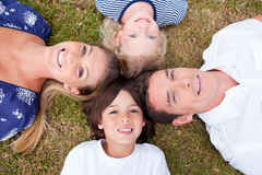 Cheerful family lying in circle on the grass Royalty Free Stock Photos