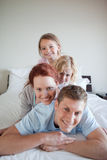 Cheerful family lying on each other Stock Photos