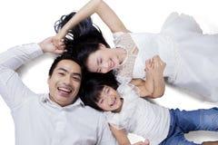 Cheerful family lying in studio Stock Photos
