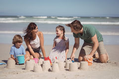 Cheerful family making sand castle at beach Stock Photos