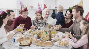 Cheerful family members saying toasts. In turn during Christmas dinner. Focus on man Royalty Free Stock Image