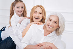 Cheerful family members sitting on the couch. Warm atmosphere. Cheerful content smiling amily members having fun and resting at home while sitting on the white Stock Image
