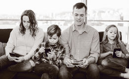 Cheerful family members spending time playing with smartphones. At home stock photography