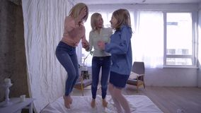 Cheerful family, mother and daughters fun jumping on bed and then hugging together on camera stock footage