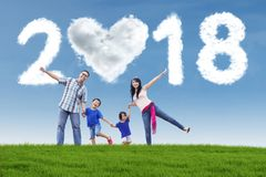 Cheerful family with numbers 2018. Image of cheerful family playing together in the meadow with clouds shaped numbers 2018 and heart in the sky royalty free stock photography