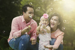 Cheerful family play with soap bubbles Stock Photo