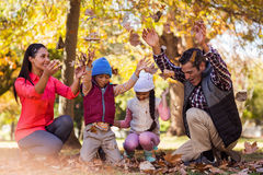Cheerful family playing with autumn leaves stock photography