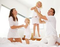 Cheerful family playing in the bedroom. Portrait of cheerful family playing on bed in the bedroom royalty free stock images