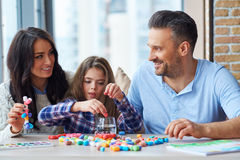 Cheerful family playing with colored set for creativity.  stock images