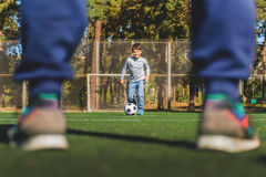 Cheerful family playing football together. Joyful child is kicking ball by leg to his father and smiling. Close up of male legs standing on field Royalty Free Stock Image