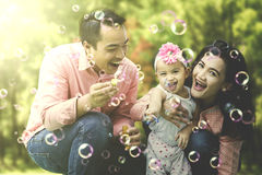 Cheerful family playing soap bubbles Stock Photography