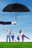Cheerful family playing under umbrella at field. Image of happy family having fun on the meadow under umbrella. Life and family insurance concept Royalty Free Stock Images