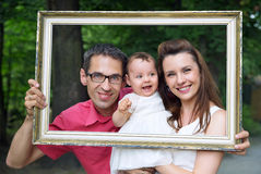 Cheerful family posing with the frame Royalty Free Stock Photos