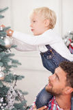 Cheerful family is preparing Christmas tree for. Cute boy is decorating New Year tree with his father. The men is holding a child on his shoulders and smiling royalty free stock images