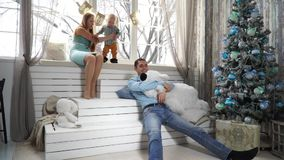 Cheerful family preparing to celebrate Christmas sitting near the winter window. Among toys stock footage