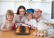 Cheerful family presenting their muffins Royalty Free Stock Image
