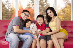 Cheerful family with puppy on the couch Royalty Free Stock Photography