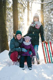 Cheerful family relaxing in the winter forest Royalty Free Stock Photos