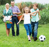 Cheerful family running with ball Stock Photos