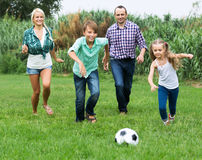 Cheerful family running with ball. Cheerful happy children and parents running with ball at sunny day Royalty Free Stock Photography