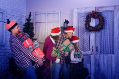 Cheerful family, in a Santa hats, goes to visit friends. At Christmas. Parents and children teenagers, with gifts in their hands, laugh and knock on the door Stock Photo