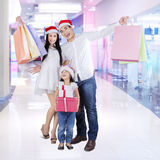 Cheerful family in shopping center. Joyful family holding shopping bags and christmas gift in the shopping center Royalty Free Stock Photos