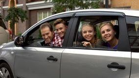 Cheerful family sitting in car and smiling into camera, auto rental, insurance royalty free stock images
