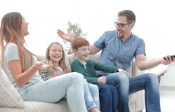 Cheerful family sitting on the couch in the living room royalty free stock images