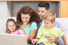 Cheerful family sitting on sofa with laptop shopping online Royalty Free Stock Images