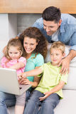 Cheerful family sitting on sofa looking at laptop Royalty Free Stock Image
