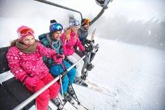 Family in ski lift going to ski terrain. Cheerful family in ski lift going to ski terrain royalty free stock photo