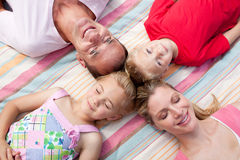 Cheerful family sleeping lying on the grass Royalty Free Stock Image