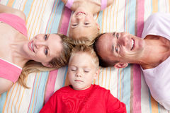 Cheerful family sleeping lying on the grass. In a park Stock Photo