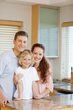 Cheerful family standing behind the kitchen counter Stock Photos
