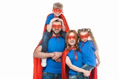 cheerful family of superheroes smiling at camera royalty free stock images
