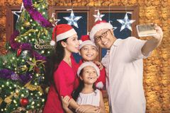 Cheerful family taking picture with Christmas tree Stock Images