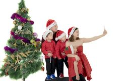 Cheerful family taking picture near Christmas tree. Cheerful family taking selfie pictures by using a smartphone near a Christmas tree, isolated on white Stock Image