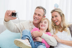 Cheerful family taking self pictures with a digital camera Royalty Free Stock Photos