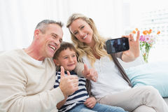 Cheerful family taking self pictures with a smartphone Royalty Free Stock Photo