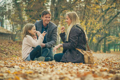 Cheerful family of three kneel on park ground covered with leaves Stock Photos