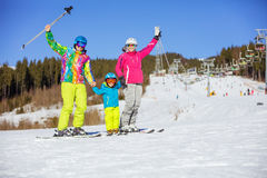 Cheerful family of three standing on ski slope Royalty Free Stock Images