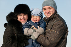 Cheerful family of three on winter walk. Closeup portrait of a mom, dad and their son while winter walk Royalty Free Stock Photos