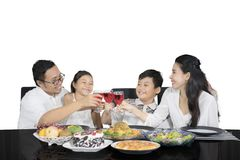 Cheerful family is toasting glasses before having meals. Picture of cheerful family toasting glasses of syrup together before having meals while sitting in the royalty free stock photo