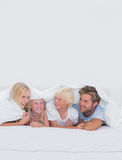 Cheerful family under the duvet Stock Images