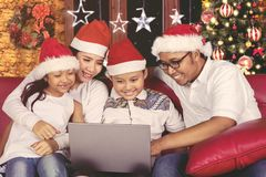 Cheerful family using a laptop at Christmas day Royalty Free Stock Photos