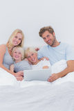 Cheerful family using a laptop in bed Stock Images
