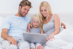 Cheerful family using a laptop in bed Royalty Free Stock Photos