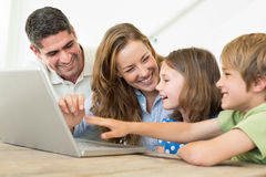 Cheerful family using laptop Stock Photography